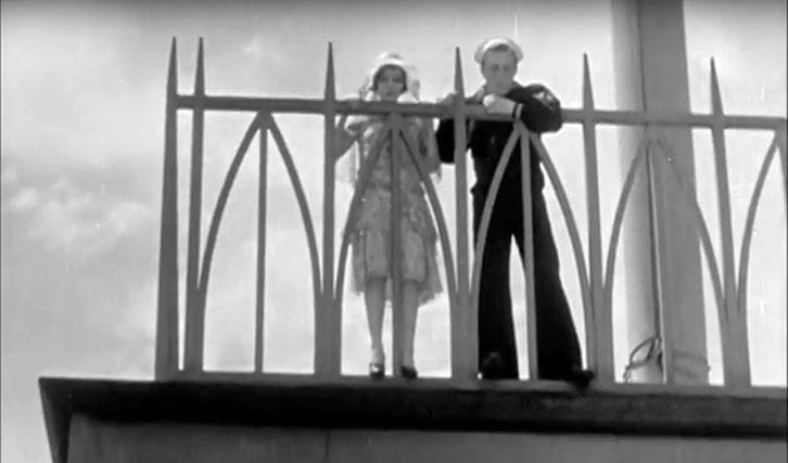 """Das junge Paar mit respektvollem Blick von oben auf die Stadt in """"Applause""""."""
