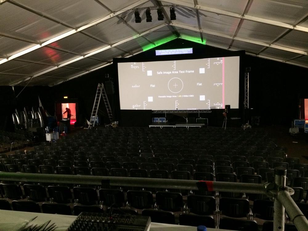 Das bestmögliche Screening erfordert Vorbereitung: Beim Internationalen Filmfestival Mannheim-Heidelberg ist auf der noch unfertigen Leinwand ein Testbild vom Digitalen Projektor zu sehen; oben sieht man schon die Untertitelprojektion, die eingerichtet wird. (© Mirjam Bromundt)